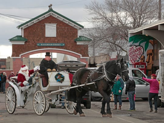 With Santa waving to visitors from his seat on the carriage, Dale Jenks of Hartland Carriage of Gasport, Niagara County, guides his horse Al around the Rochester Public Market as part of the opening Sunday of the annual Holidays at the Market event.