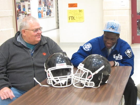 Central York football coach Brad Livingston shares a laugh with Andrews Dadeboe as he signs his letter of intent. (SUBMITTED, ERIN O'NEILL -- THE PROWLER)