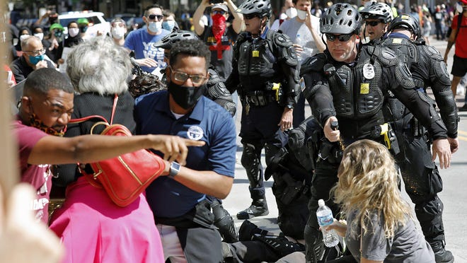 Columbus City Council President Shannon Hardin, left, and Franklin County Commissioner Kevin Boyce, in blue shirt, help Congresswomen Joyce Beatty after they were pepper sprayed while trying to intervene as Columbus Police use pepper spray on protesters during a protest at on High Street near the Ohio Statehouse on May 30.
