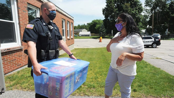 Lana Sartre, a town resident, delivers a container filled with food to Raynham police officer Mike Civale, on Friday  June 12, 2020.