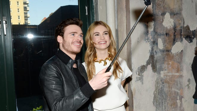 """Actors Richard Madden and Lily James take a selfie while attending AOL's BUILD Speaker Series to discuss their new film """"Cinderella"""" at AOL Studios on Monday, March 9, 2015, in New York."""