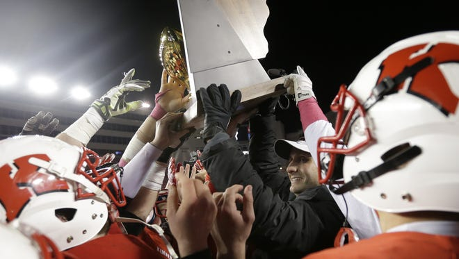 Kimberly High School head coach Steve Jones hoists the championship trophy after the Papermaker's 31 to 6 victory over Arrowhead High School during the 2014 WIAA Division 1 championship football game on November 21, 2014, in Madison.