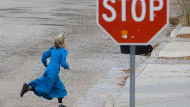 In this Dec. 16, 2014, file photo, a girl runs past a street sign in Hildale, Utah.