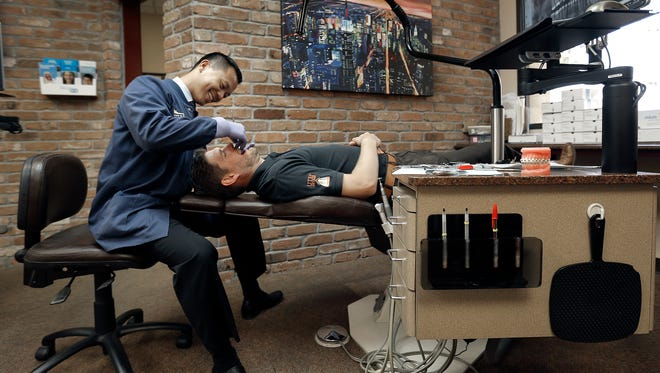 El Paso Orthodontist Dr. Jesse Teng of Mundy & Teng Orthodontics was recently named president of the Texas Association of Orthodontists. Above, Dr. Teng checks Ricky Lee Nichols' braces during a recent visit to his office at 5551 N. Mesa.