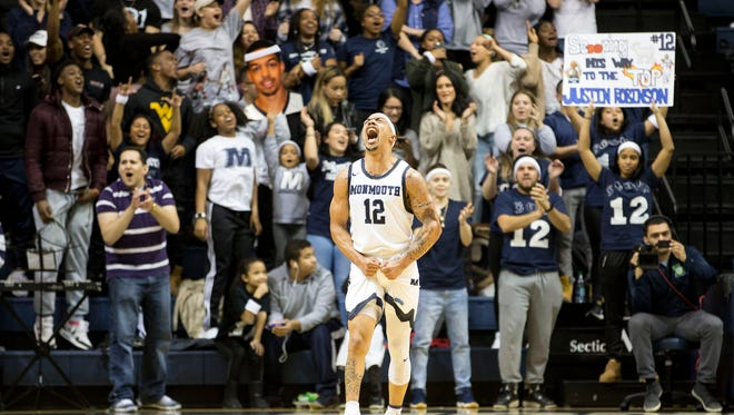 Monmouth's Justin Robinson celebrates after the game for being the top scorer in Monmouth University history.