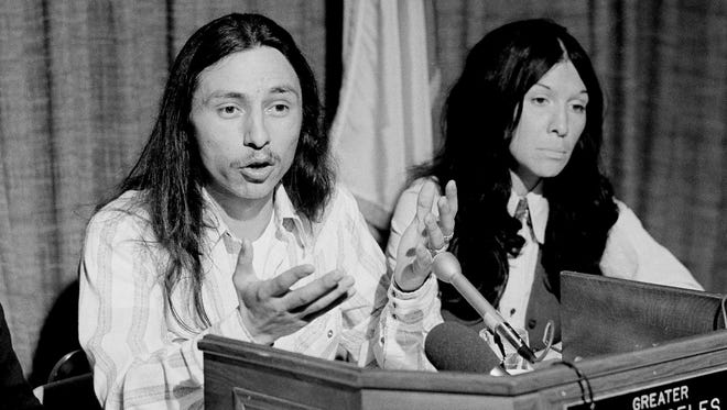 John Trudell, left, national chairman of the American Indian Movement, AIM, flanked by singer Buffy St. Marie during a news conference in Los Angeles on March 7, 1975. Trudell, a poet and actor who spoke for American Indian protesters during the 1969 Alcatraz Island occupation and later headed the American Indian Movement, has died at age 69. A trustee of Trudell's estate, Cree Miller, says he died of cancer on Tuesday, Dec. 8, 2015, at his home in Santa Clara County in Northern California.