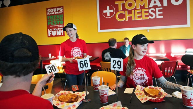 Madi Sanders delivers food to other members of the Tom+Chee staff as they undergo training in March at the Darboy restaurant. The new business received multiple stamps of approval from readers.