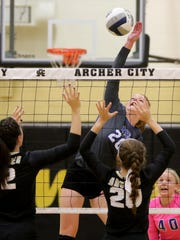 Windthorst's Brynlee Wolf spikes the ball against Archer