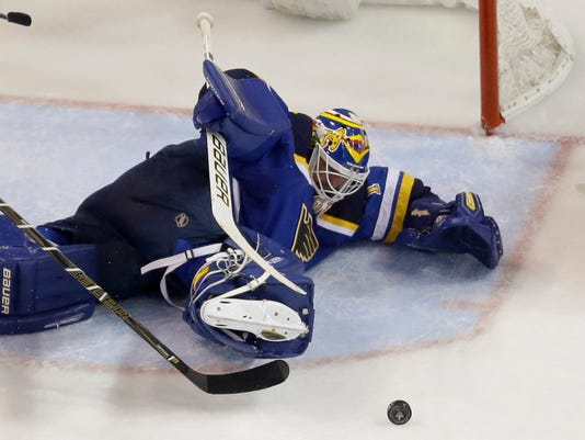 St. Louis Blues goalie Brian Elliott keeps his eye on the puck during the second period in Game 2 of an NHL hockey first-round Stanley Cup playoff series against the Chicago Blackhawks, Friday, April 15, 2016, in St. Louis. (AP Photo/Jeff Roberson)