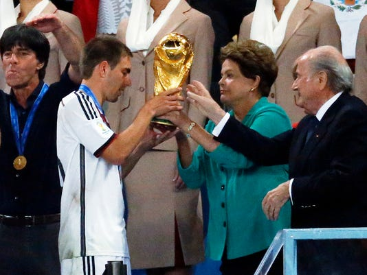 Germany's team captain Philipp Lahm, second left, receives the World Cup trophy by Brazil's President Dilma Rousseff and FIFA President Sepp Blatter, right, during the World Cup final soccer match between Germany and Argentina at the Maracana Stadium in Rio de Janeiro, Brazil, Sunday, July 13, 2014. (AP Photo/Frank Augstein)