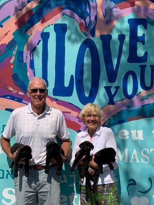 Greg and Betty Ryberg hold foster puppies Scooby, Rubble, Clover and Berrie.