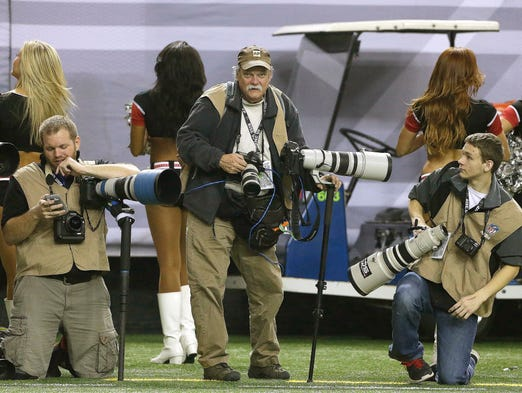 In this  Sunday, Dec. 29, 2013, photo, AP Photographer Dave Martin, center, works during the first half of an NFL football game between the Carolina Panthers and the Atlanta Falcons, in Atlanta. Martin, a longtime Associated Press photographer based in Montgomery, Ala., died after collapsing on the Georgia Dome field at the Chick-fil-A Bowl on Tuesday, Dec. 31, 2013. Martin was 59.Here are some photos from his long career:
