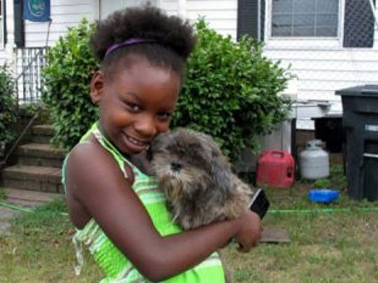 Regina Harrell, 9, holds her dog Roscoe outside her home in North Augusta, S.C. on Monday, July 21, 2014. Regina was taken from her home and her mother Debra Harrell was charged with a felony after she left her daughter alone to play at a nearby park while she worked at McDonald's.