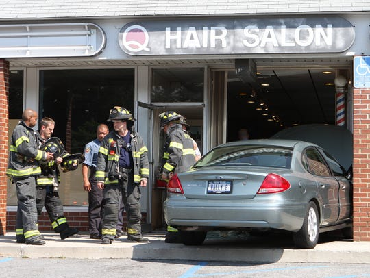 New Rochelle firefighters and police investigate a car that was driven into the storefront of George's Hair Salon in the Quaker Ridge Shopping Center in New Rochelle Wednesday afternoon, June 15, 2011. It didn't appear that there were any serious injuries. (Mark Vergari/The Journal News)