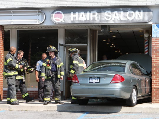 New Rochelle firefighters and police investigate a car that was driven into the storefront of George's Hair Salon in the Quaker Ridge Shopping Center in New Rochelle Wednesday afternoon, June 15, 2011.  It didn't appear that there were any serious injuries. ( Mark Vergari / The Journal News )