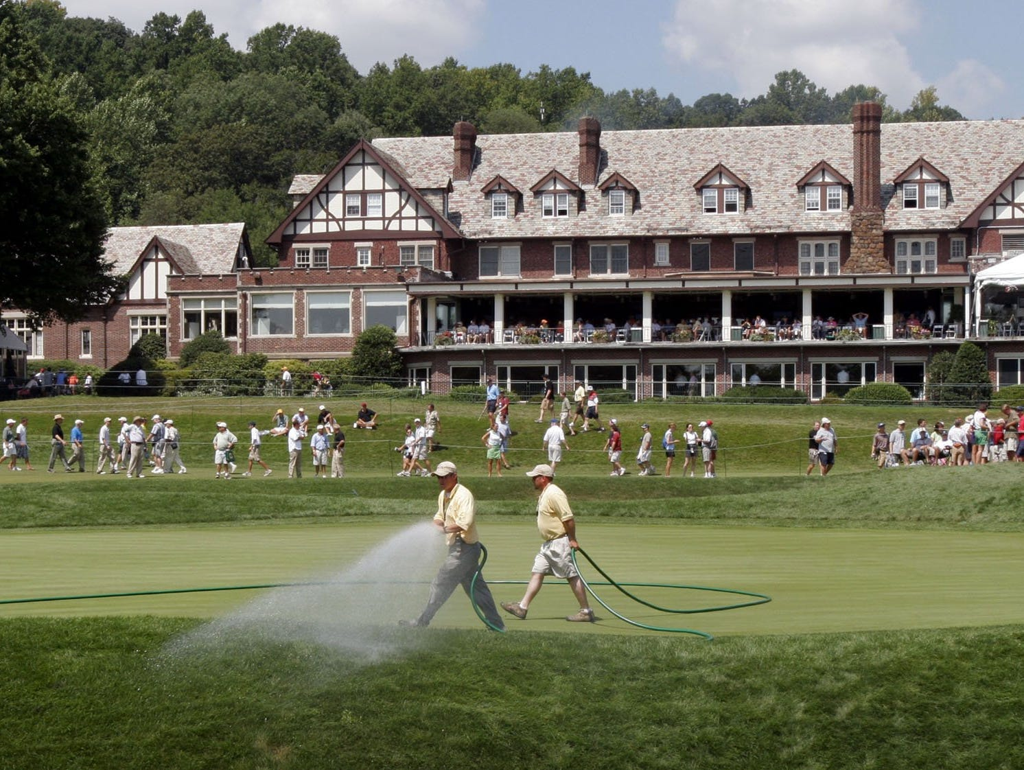 In this file photo, the grounds crew sprays water on the 18th green in front of the clubhouse, during the practice round Wednesday at the 87th PGA Championship at the Baltusrol Golf Club in Springfield, New Jersey,