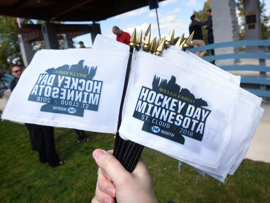 Small Hockey Day Minnesota flags are handed out during