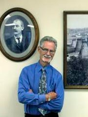 Third-generation employee and sales manager Nelson McKee stands next to a photo of Victor Insulators founder Fred Locke and a plant photo from the 1930s at plant in Victor.