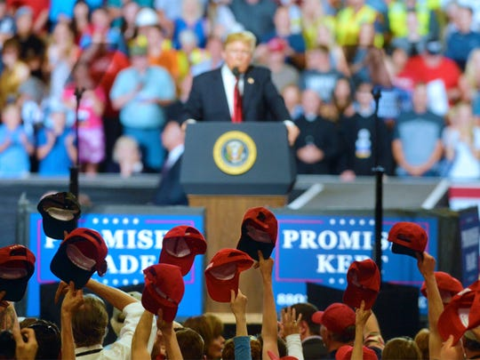 Rally goers tip their hats to President Donald Trump during his Great Falls campaign rally in the Four Seasons Arena on Thursday, July 5, 2018