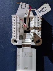 The UWP mount on the Honeywell Lyric T5 Wi-Fi Thermostat with wires marked from the previous installation. The mount includes a leveling point, a wire length gauge and switches that explain their functions in place of jumper wires common in thermostats.