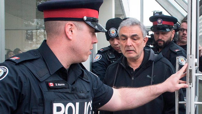 Vahe Minassian, father of Alek Minassian, is surrounded by members of the media as he leaves court with a police escort in Toronto on April 24, 2018.