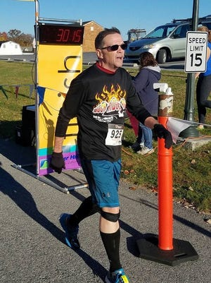 Chambersburg's Dave McLucas crosses the finish line of last weekend's Menno Haven 5K Run/Walk for Alzheimer's. McLucas, who hit a PR in the race, has come all the way back from nearly a year ago, when he suffered sudden cardiac arrest.