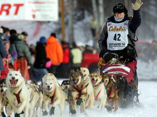 In this 2006 photo, musher Rachael Scdoris, of Bend, Ore., waves to the crowd as she drives her dog team down the starting chute of the Iditarod Trail Sled Dog Race.