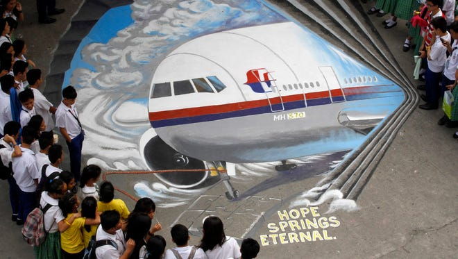 Filipino artists from the Guhit Visual Arts Group painted an image of Malaysia Airlines Flight MH370 at the Benigno Ninoy Aquino High School grounds in Makati City, south of Manila, Philippines, 17 March 2014 to express hope and solidarity for the passengers and crew  of the missing Malaysia Airlines flight 370.