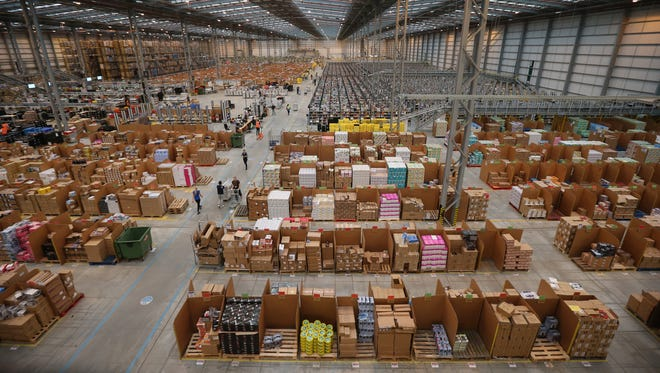 Employees select and dispatch items in the huge Amazon 'fulfilment centre' warehouse on Thursday in Peterborough, England.