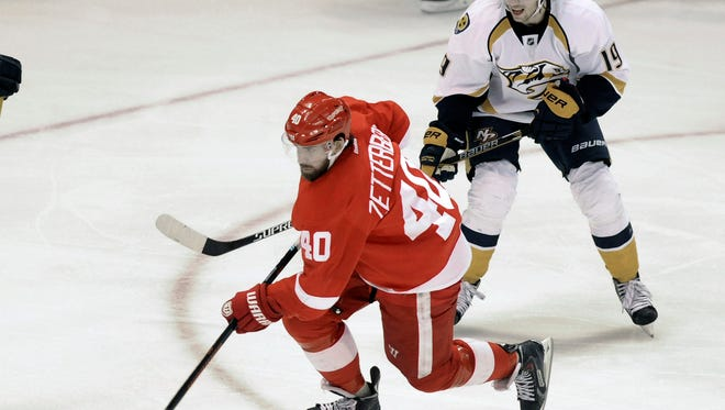 Detroit Red Wings left wing Henrik Zetterberg (40), middle, goes to the net in between Nashville Predators defenseman Seth Jones (3), left, and center Calle Jarnkrok (19) during the third period of an NHL hockey game in Detroit, Saturday, Jan. 17, 2015.  The Red Wings defeated the Predators 5-2.