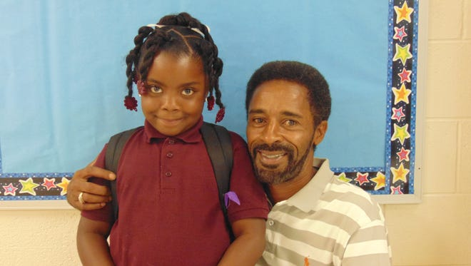 Aa'ionni Sydnor and her grandfather, Frederick Sydnor, participated in a reading celebration at Quarter Mile Lane School.