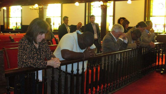 United Way CEO Margaret Trahan and LCG Councilman Kenneth Boudreaux pray at the altar of the Emanuel A.M.E. church in Charleston to honor the victims of a mass shooting there.