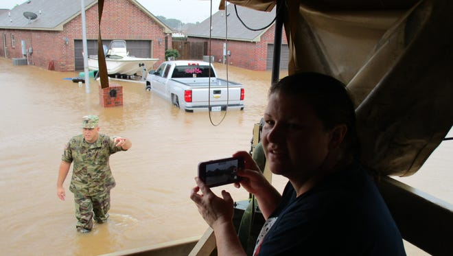 Dana Broussard takes a picture of her flooded home in Highland Ridge as the National Guard evacuates her family.