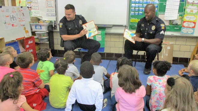 """Officer Mark Boggs and Sgt. Patrick Williams of the Mansfield Police Department read """"Green Eggs and Ham"""" to kindergarten students at Woodland Elementary School."""