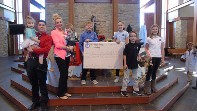 St. Mary's Springs Academy created cards to benefit the family of Levi Schwantes. Holy Family and SMSA raised $3,067. Pictured are, from left: Brooklyn Schwantes, Dan Schwantes, Karissa Schwantes, Levi Schwantes, Billy Everson, Grace Coon, Cooper Krug and Riley Gilgenbach.