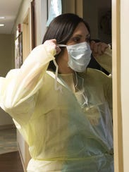Laura Breedlove puts on protective apparel while working
