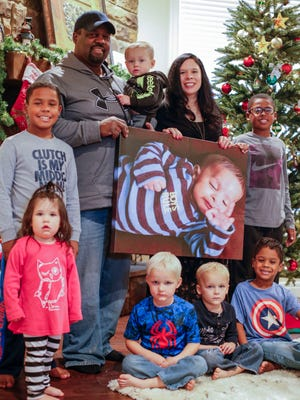 Eric and Elizabeth Washington hold a photo of their son Dante, who died of a rare disorder that doctors determined to be brainstem disconnection syndrome, while surronded by their other children (from bottom left) Journey, 2, Brayden, 4, Ryder, 4, Denzel, 6, (from top left) Deric, 9, Jamie, 1, and Darian, 11.