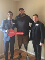 Michael K. Cain is flanked by Kesh Patel (left), a Wells Fargo community banking district manager; and Thomas Beck (right), a Wells Fargo branch manager in Waynesboro, after being given a ceremonial key to his Stuarts Draft home.
