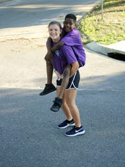 Catholic High School student Tori Toellner gives Cameron Bell a piggy-back ride during last year's Sunset Run. Tori was part of a group of CHS runners who volunteered to run with special needs students in the Morning Star program.