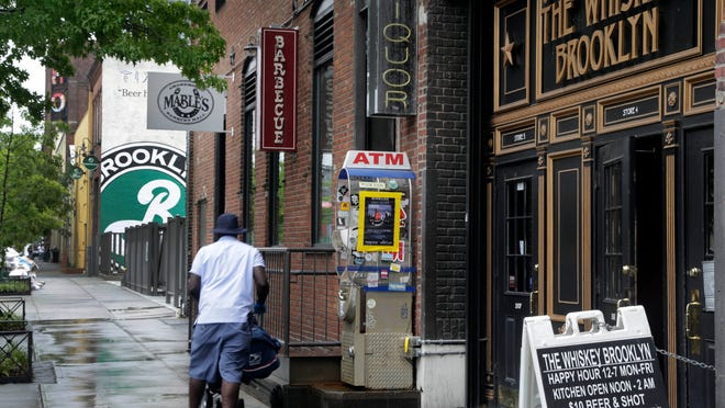 In this July 1, 2013 file photo, restaurants line the street adjacent to the Brooklyn Brewery, in the Williamsburg section of Brooklyn. Many neighborhoods around the world are comparing themselves to Brooklyn.