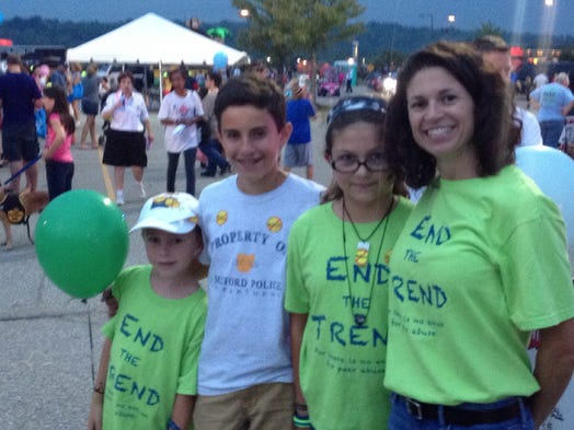 """Milford Mayor Laurie Howland with her daughter, Alex Walter, 12, near a booth where the girl was advertising her anti-bullying initiative called """"End the Trend."""" With them are the sons of Milford City Manager Jeff Wright. Camden Wright, 7, is at far left and Nicholas Wright, 13, is next to him."""