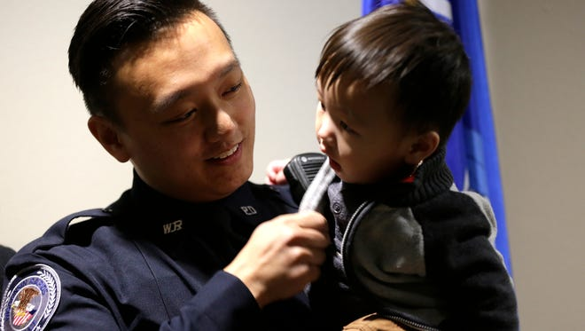 Officer Fue Khang, the first Hmong officer for the city of Wisconsin Rapids, plays with his child Thaajyeeb Axel, 1, after being sworn in at the Wisconsin Rapids City Hall building, Tuesday, November 16, 2016.