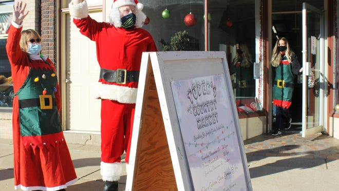 Kelly Hostetler, executive director of St. Joseph County United Way, and Santa draw customers to the Christmas pop -up store Thursday in downtown Sturgis.