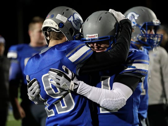 Green Bay Southwest's Noah Schmidt (19) and Nathan Steinbrecker embrace after a 35-14 loss against Waunakee in a WIAA Division 2 state semifinal football game at Calder Stadium in Menasha.