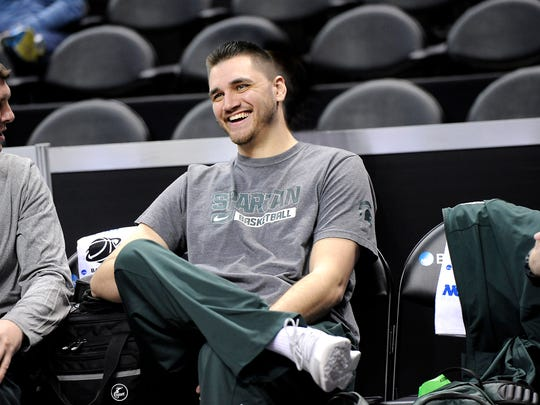 Former MSU basketball player Alex Gauna watches from the bench the Spartans practice for the NCAA tournament Thursday in Charlotte, N.C.