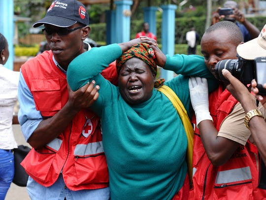 Kenya Red Cross staff assist a woman after she viewed