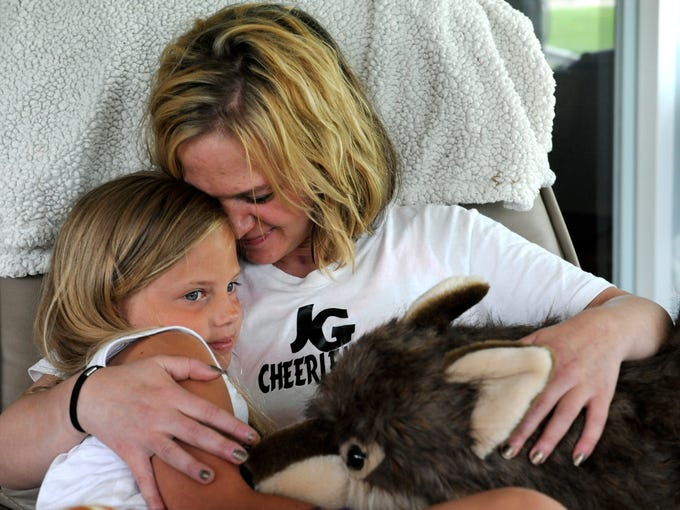 Stephanie Latier embraces her daughter, Lily, 8, at