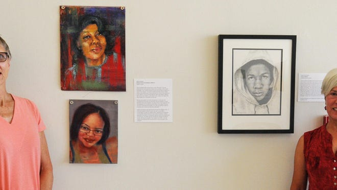 Members of the Kansas Figure Drawing Group Debbie Wagner and Maria Ames Kuiper stand beside their portraits of Black people who have died by police brutality in the Salina Responds #blacklivesmatter gallery at the Salina Art Center that will be on display during the month of August.
