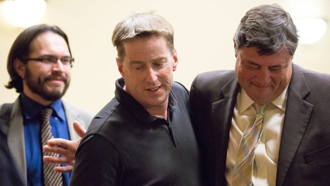 Ross Flynn, center, embraces his attorney Jeff Lahann, right, as associate attorney Chris Cardenas looks on Thursday, April 7, 2016, in 3rd Judicial District Court after a jury found Flynn not guilty of aggravated assault and assault on an officer. Flynn was convicted on a charge of evading arrest.