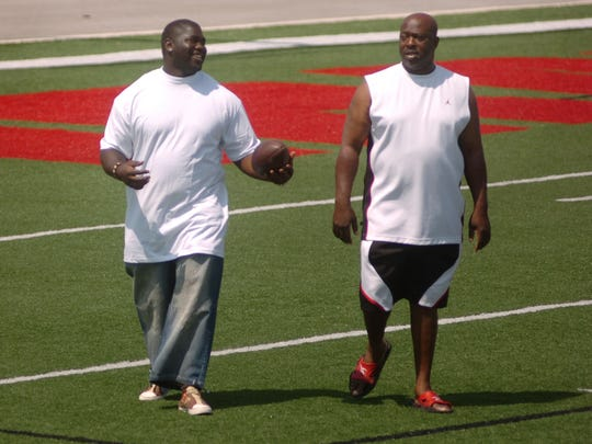 Joe Cohen, left, walks with his father Melvin Byrd as they talk together at Palm Bay High School. Byrd is one of the coaches with the Ravens.